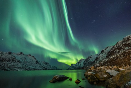 Northern lights over the snowy mountains and body of water