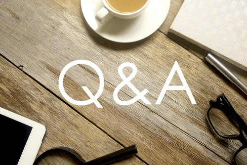 Q&A on wooden table with tea, ipad and glasses
