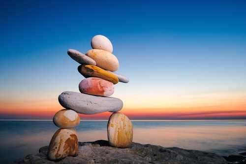 Sunset over the water with stones stacked on each other