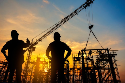 Two men in hard hats with large cranes in sunset