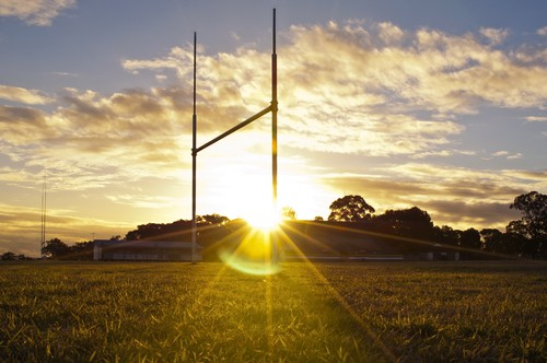 Field with goal posts and sunset